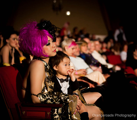 Violet Eva watches the pageant with her son.  ©OrangeRoads Photography