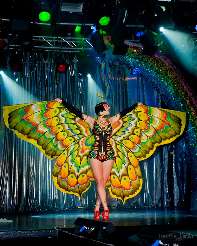 Cleo Viper spreading her wings under the glittering rainbow.  © Tuomas Lairila   (Helsinki Burlesque Festival)